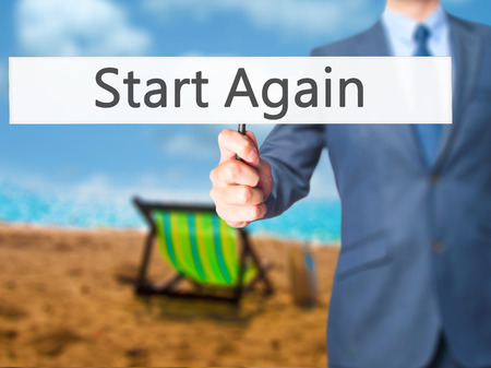 displacement: Start Again - Businessman hand holding sign. Business, technology, internet concept. Stock Photo