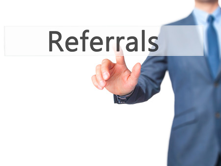 referrals: Referrals - Businessman hand pressing button on touch screen interface. Business, technology, internet concept. Stock Photo Stock Photo