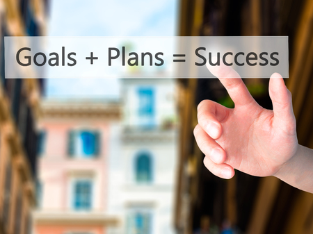 strategic focus: Goals  Plans  Success - Hand pressing a button on blurred background concept . Business, technology, internet concept. Stock Photo