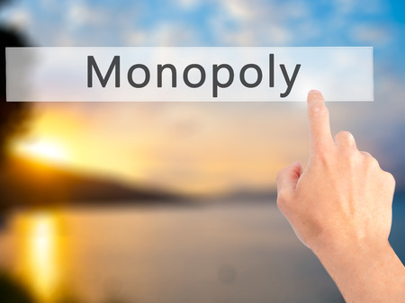 Monopoly - Hand pressing a button on blurred background concept . Business, technology, internet concept. Stock Photo