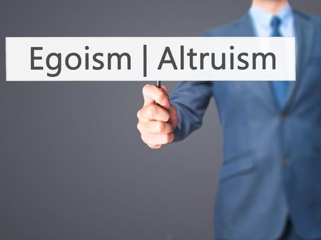 altruismo: Altruismo Egoísmo - hombre de negocios mano que sostiene la señal. Negocios, la tecnología, el concepto de internet. Foto de stock