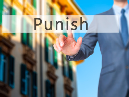 enforcing the law: Punish - Businessman hand pressing button on touch screen interface. Business, technology, internet concept. Stock Photo