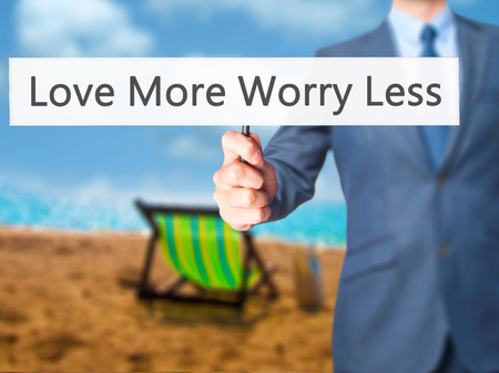 in need of space: Love More Worry Less - Businessman hand holding sign. Business, technology, internet concept. Stock Photo
