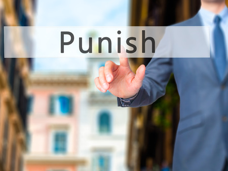 discouraging: Punish - Businessman hand pressing button on touch screen interface. Business, technology, internet concept. Stock Photo