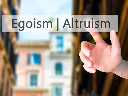 altruism: Altruism  Egoism - Hand pressing a button on blurred background concept . Business, technology, internet concept. Stock Photo Stock Photo