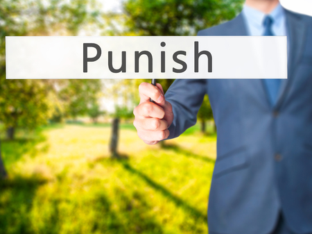 law enforcing: Punish - Businessman hand holding sign. Business, technology, internet concept. Stock Photo
