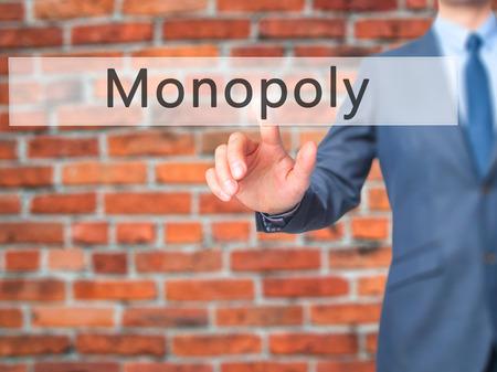 monopoly: Monopoly - Mano de empresario botón en la interfaz de pantalla táctil de prensado. Negocios, la tecnología, el concepto de internet. Foto de stock