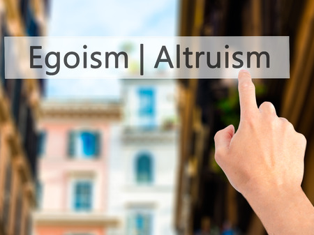 egoist: Altruism  Egoism - Hand pressing a button on blurred background concept . Business, technology, internet concept. Stock Photo Stock Photo