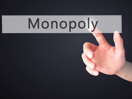 monopoly money: Monopoly - Hand pressing a button on blurred background concept . Business, technology, internet concept. Stock Photo