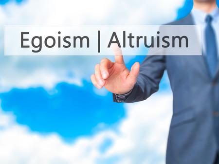 altruismo: Altruism  Egoism - Businessman hand pressing button on touch screen interface. Business, technology, internet concept. Stock Photo