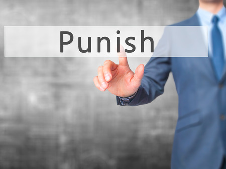 enforcing: Punish - Businessman hand pressing button on touch screen interface. Business, technology, internet concept. Stock Photo