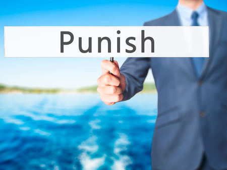 fined: Punish - Businessman hand holding sign. Business, technology, internet concept. Stock Photo