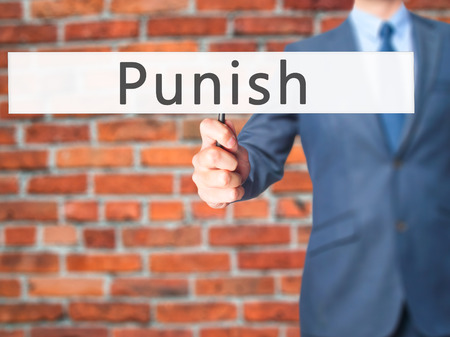 forgiven: Punish - Businessman hand holding sign. Business, technology, internet concept. Stock Photo