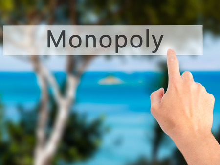 monopolio: Monopoly - Hand pressing a button on blurred background concept . Business, technology, internet concept. Stock Photo