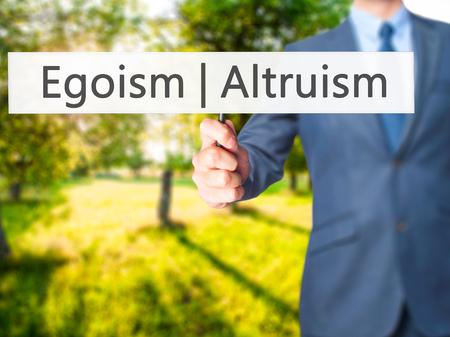 altruismo: Altruismo Ego�smo - hombre de negocios mano que sostiene la se�al. Negocios, la tecnolog�a, el concepto de internet. Foto de stock