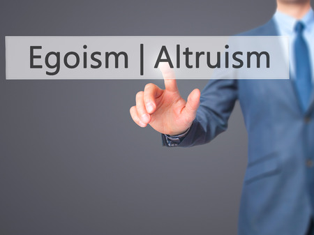 altruismo: Altruism  Egoism - Businessman hand pressing button on touch screen interface. Business, technology, internet concept. Stock Photo