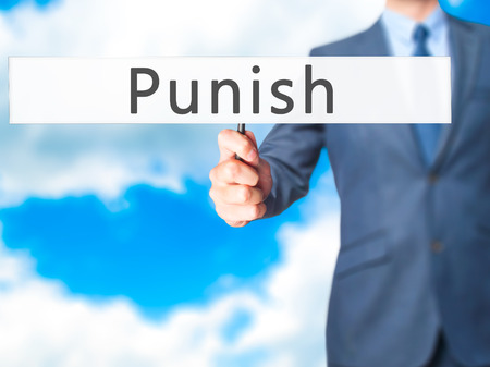 enforcing: Punish - Businessman hand holding sign. Business, technology, internet concept. Stock Photo
