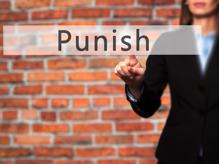 enforced: Punish - Businesswoman hand pressing button on touch screen interface. Business, technology, internet concept. Stock Photo