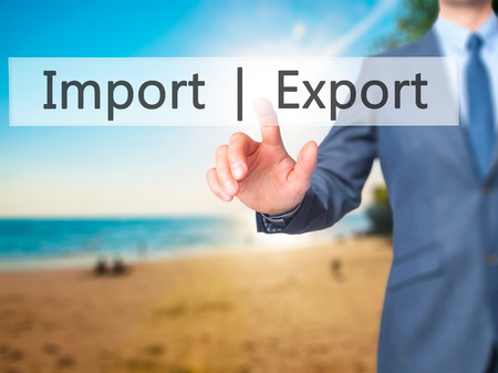 exportation: Import  Export - Businessman hand pressing button on touch screen interface. Business, technology, internet concept. Stock Photo Stock Photo