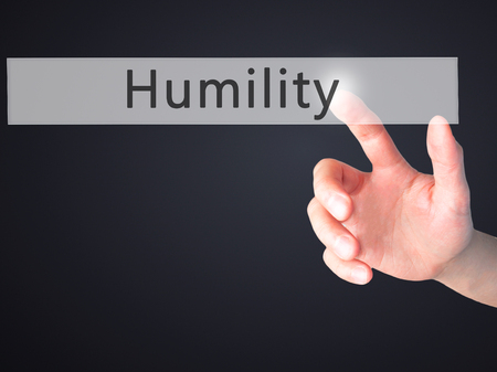 singleness: Humility - Hand pressing a button on blurred background concept . Business, technology, internet concept. Stock Photo