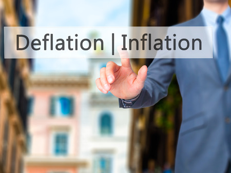 deflation: Deflation Inflation - Businessman hand pressing button on touch screen interface. Business, technology, internet concept. Stock Photo