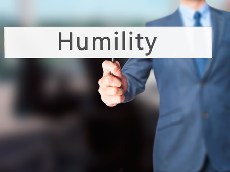 humildad: Humility - Businessman hand holding sign. Business, technology, internet concept. Stock Photo