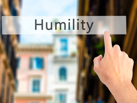 humility: Humility - Hand pressing a button on blurred background concept . Business, technology, internet concept. Stock Photo