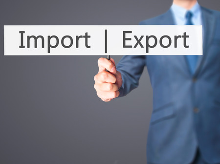 exportation: Import  Export - Businessman hand holding sign. Business, technology, internet concept. Stock Photo
