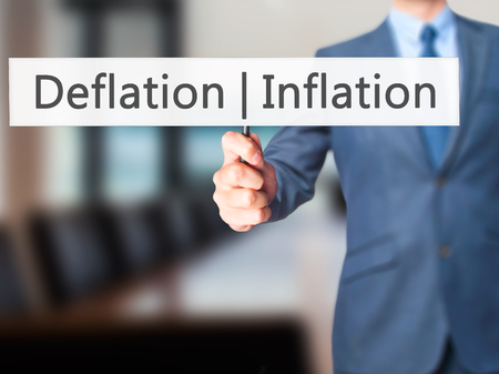 deflation: Deflation Inflation - Businessman hand holding sign. Business, technology, internet concept. Stock Photo Stock Photo