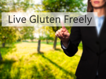 freely: Live Gluten Freely - Businesswoman hand pressing button on touch screen interface. Business, technology, internet concept. Stock Photo