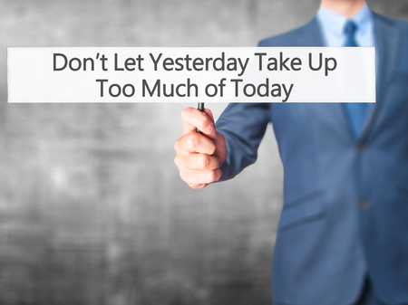 yesterday: Dont Let Yesterday Take Up Too Much of Today - Businessman hand holding sign. Business, technology, internet concept. Stock Photo