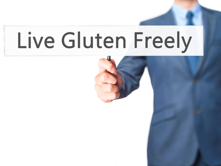 nota: Live Gluten Freely - Businessman hand holding sign. Business, technology, internet concept. Stock Photo Stock Photo
