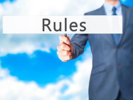 credible: Rules - Businessman hand holding sign. Business, technology, internet concept. Stock Photo