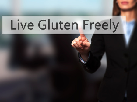 nota: Live Gluten Freely - Businesswoman hand pressing button on touch screen interface. Business, technology, internet concept. Stock Photo