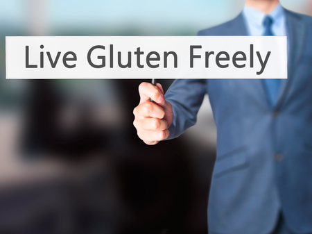 freely: Live Gluten Freely - Businessman hand holding sign. Business, technology, internet concept. Stock Photo Stock Photo