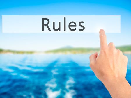 credible: Rules - Hand pressing a button on blurred background concept . Business, technology, internet concept. Stock Photo