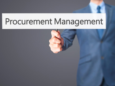 procure: Procurement Management - Businessman hand holding sign. Business, technology, internet concept. Stock Photo