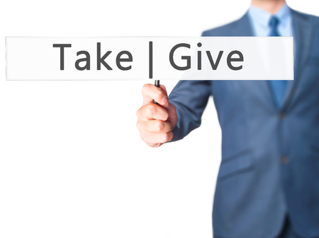 Give  Take - Businessman hand holding sign. Business, technology, internet concept. Stock Photo