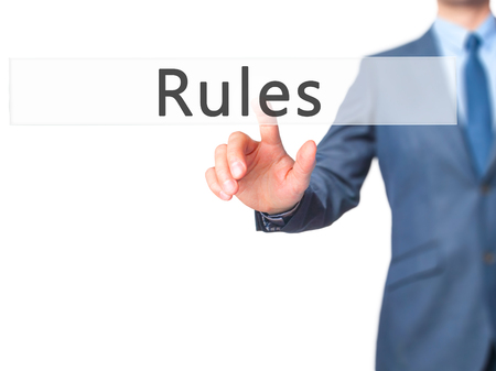 credible: Rules - Businessman hand pressing button on touch screen interface. Business, technology, internet concept. Stock Photo