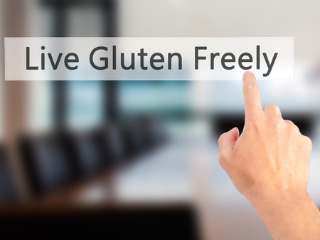 freely: Live Gluten Freely - Hand pressing a button on blurred background concept . Business, technology, internet concept. Stock Photo Stock Photo