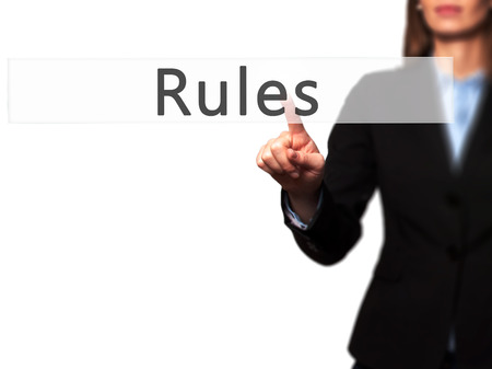 credible: Rules - Businesswoman hand pressing button on touch screen interface. Business, technology, internet concept. Stock Photo