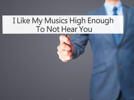 unloved: I Like My Musics High Enough To Not Hear You - Businessman hand holding sign. Business, technology, internet concept. Stock Photo