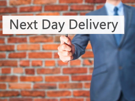 ship order: Next Day Delivery - Businessman hand holding sign. Business, technology, internet concept. Stock Photo Stock Photo