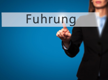 powerful creativity: Fuhrung (Leadership in German) - Businesswoman hand pressing button on touch screen interface. Business, technology, internet concept. Stock Photo
