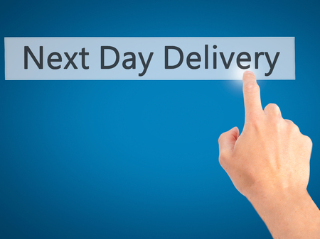 ship order: Next Day Delivery - Hand pressing a button on blurred background concept . Business, technology, internet concept. Stock Photo