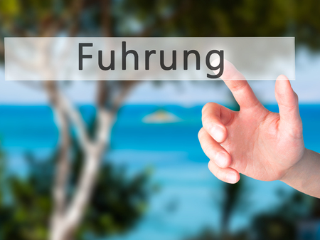 fulfill: Fuhrung (Leadership in German) - Hand pressing a button on blurred background concept . Business, technology, internet concept. Stock Photo