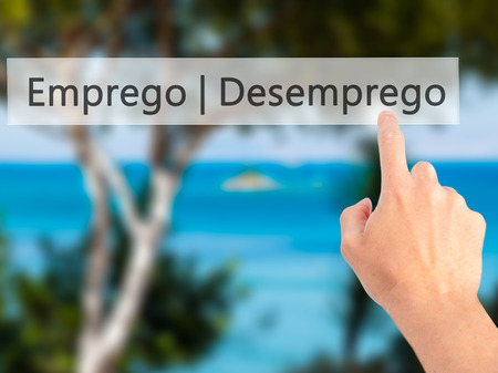 need direction: Emprego Desemprego (Employment - Unemployment in Portuguese) - Hand pressing a button on blurred background concept . Business, technology, internet concept. Stock Photo Stock Photo