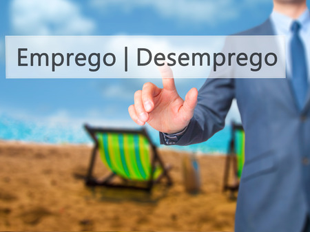 need direction: Emprego Desemprego (Employment - Unemployment in Portuguese) - Businessman hand pressing button on touch screen interface. Business, technology, internet concept. Stock Photo