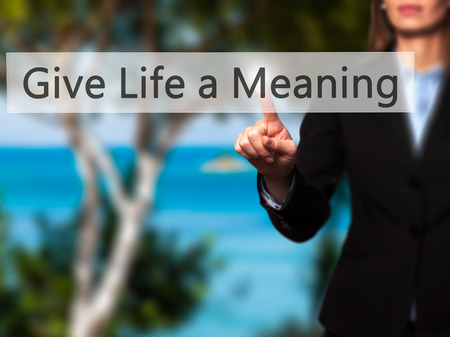 Give Life a Meaning - Businesswoman hand pressing button on touch screen interface. Business, technology, internet concept. Stock Photo
