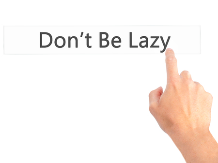 procrastination: Dont Be Lazy - Hand pressing a button on blurred background concept . Business, technology, internet concept. Stock Photo